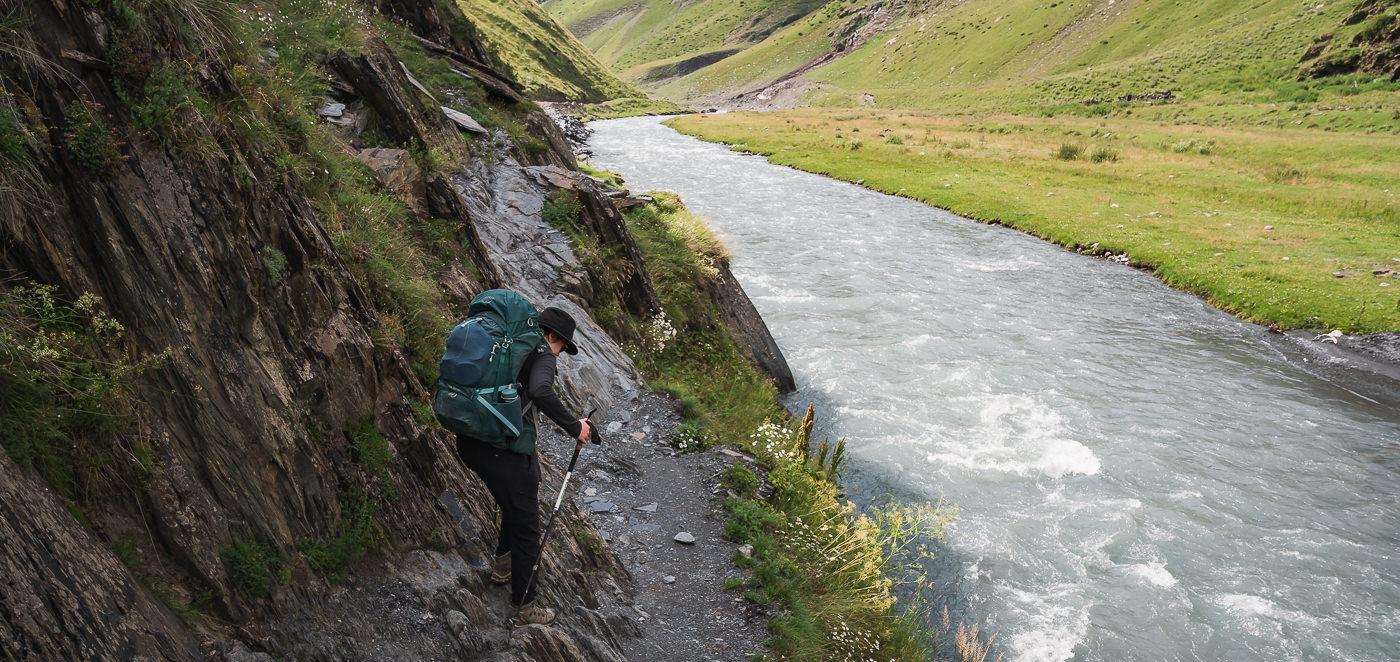 A hiker scrambles along the rocky riverside trail near Girevi on the Shatili Omalo trek in Georgia