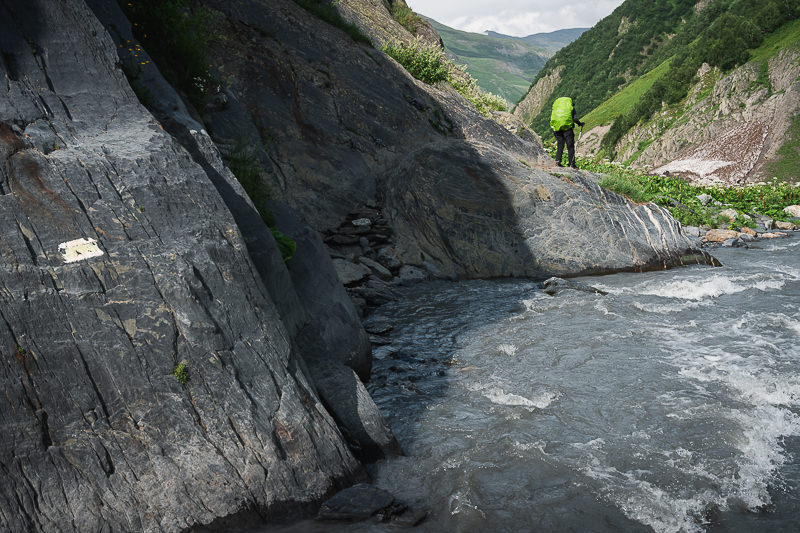 A hiker climbs over the rocky trail next to a fast flowing river on the Shatili Omalo trek in Georgia