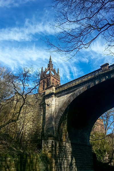 Ultimate Glasgow Guide: Looking up to an old bridge and church steeple on the Kelvin River Walkway, Glasgow