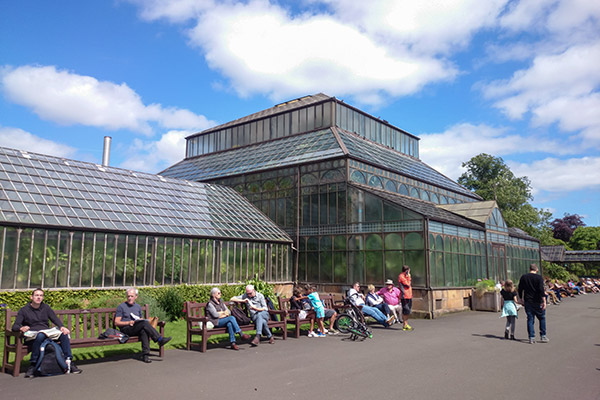 Ultimate Glasgow Guide: People sitting on benches outside the glasshouse at the Botanic Gardens on a sunny day, Glasgow