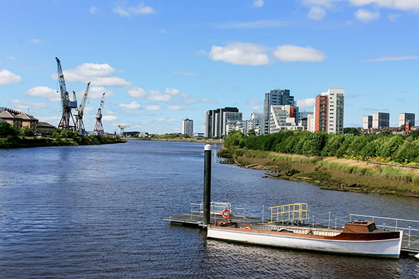 Ultimate Glasgow Guide: A small boat and cranes in the background on the River Clyde, Glasgow