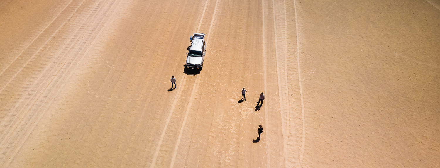 A drone shot looking down on four people and a Toyota Landcruiser alone in the Gobi Desert, Mongolia