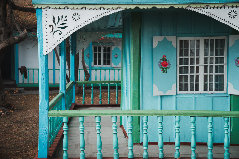 The wood of the Doukhobor museum house is painted in green and blue and bordered by carved designs