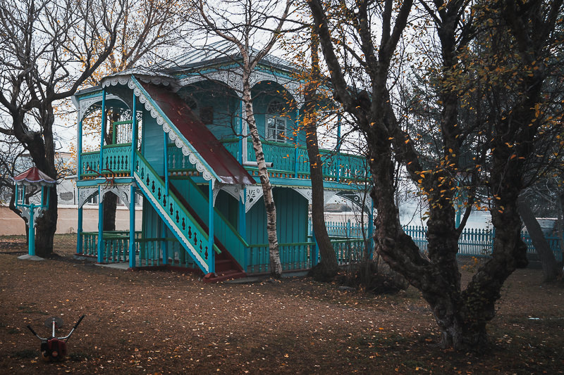 A two storey pale blue and green wooden museum house in Gorelovka, once a Doukhobor orphanage