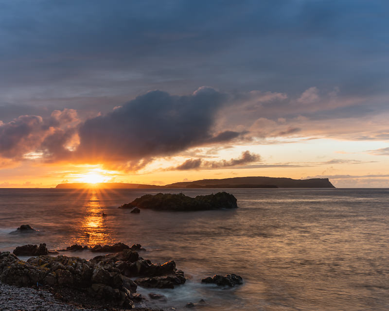 A view of the sun setting behind Canna from Guirdil Bay on the west coast of Rum