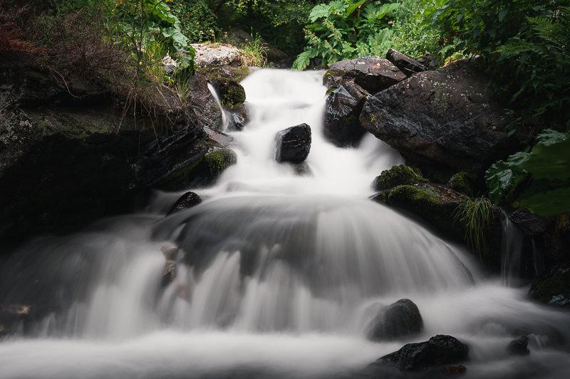 The river spilling down over rocks next to the Big Gveleti Waterfall trail in Kazbegi
