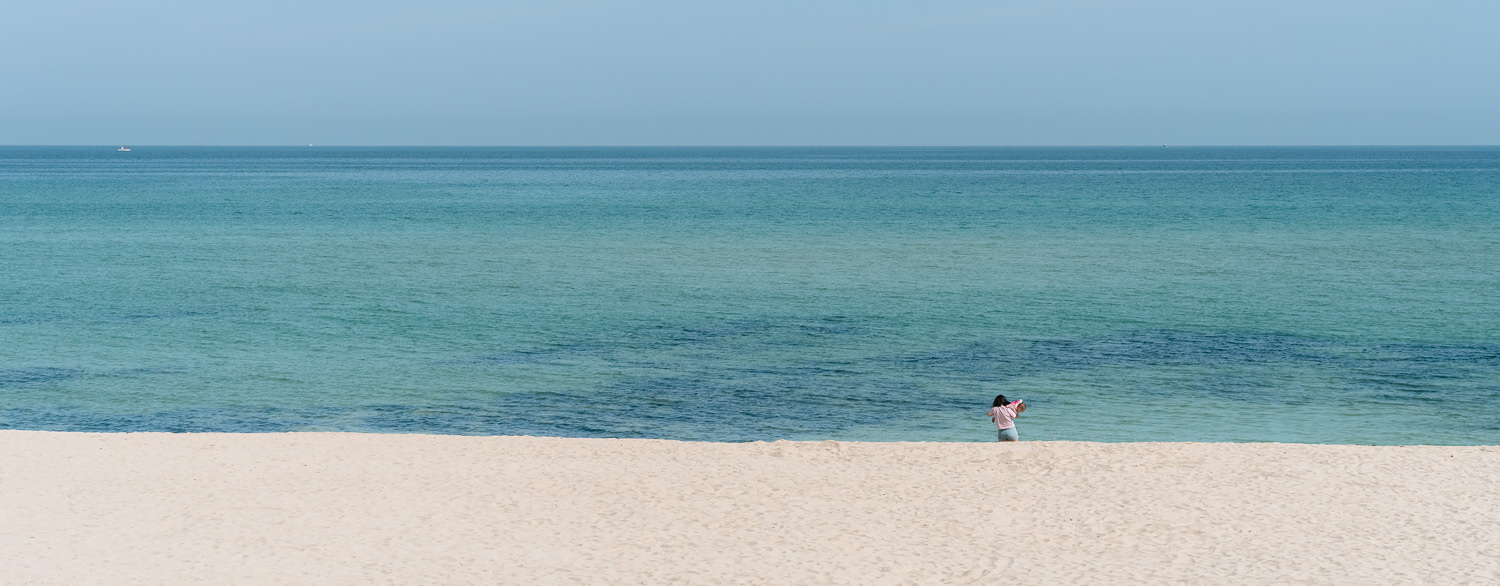 A woman holds her child in front of the blue sea and sky on the white sand of Gwakji Beach on Jeju Island in Korea