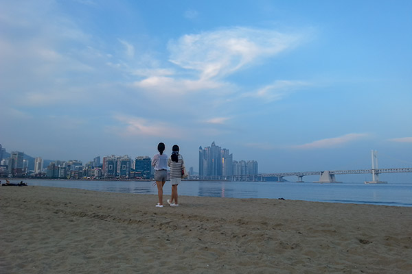 Busan City Guide: Two women strolling the beach at sunset at Gwangalli Beach