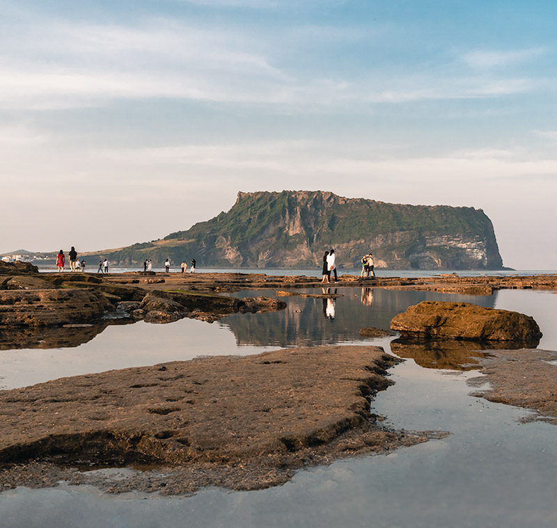 People reflected in rock pools at sunset, with the towering rock of Seongsan Ilchulbong rising behind on Jeju Island