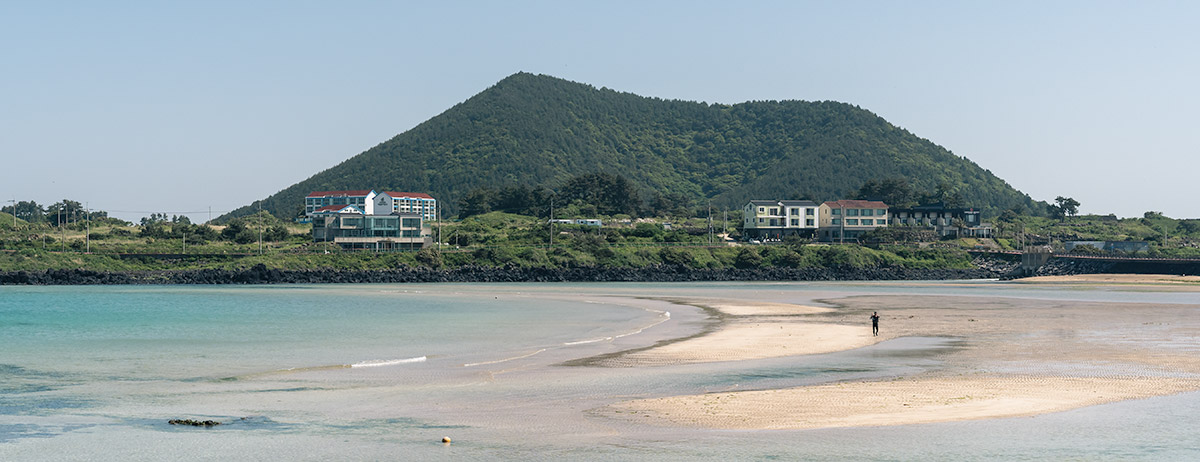 Hado Beach spreads out in front of Jimi-bong, an oreum covered in green trees