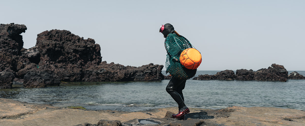 One of the haenyeo divers walking on a rocky shore with her catch in a net and orange flotation buoy slung over her shoulder