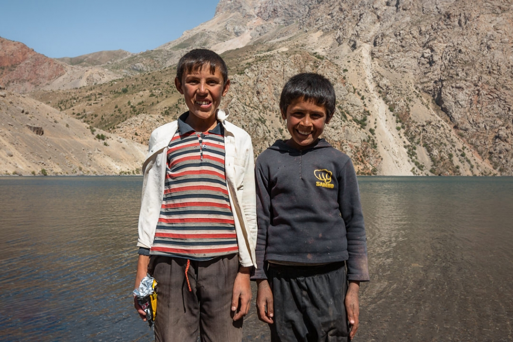 Two smiling local boys standing in front of Hazorchazma, the seventh lake of the Haft Kul in the Fann Mountains in Tajikistan.