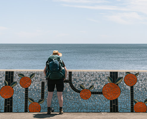 A female Olle Trail hiker standing by a Hallabong mosaic mural, looking out to sea on Jeju Island
