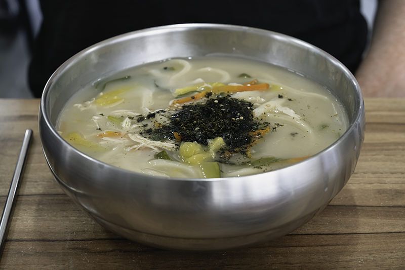 A large stainless steel bowl of chicken handcut noodles at the famous Hallim Kalguksu in Hallim, Jeju