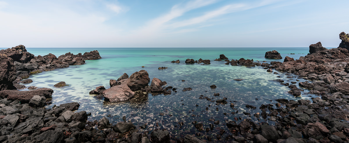 A wide view of a mall black rocky bay with clear aquamarine water at the Hangdam Coastal Walkway on the Jeju Olle Trail