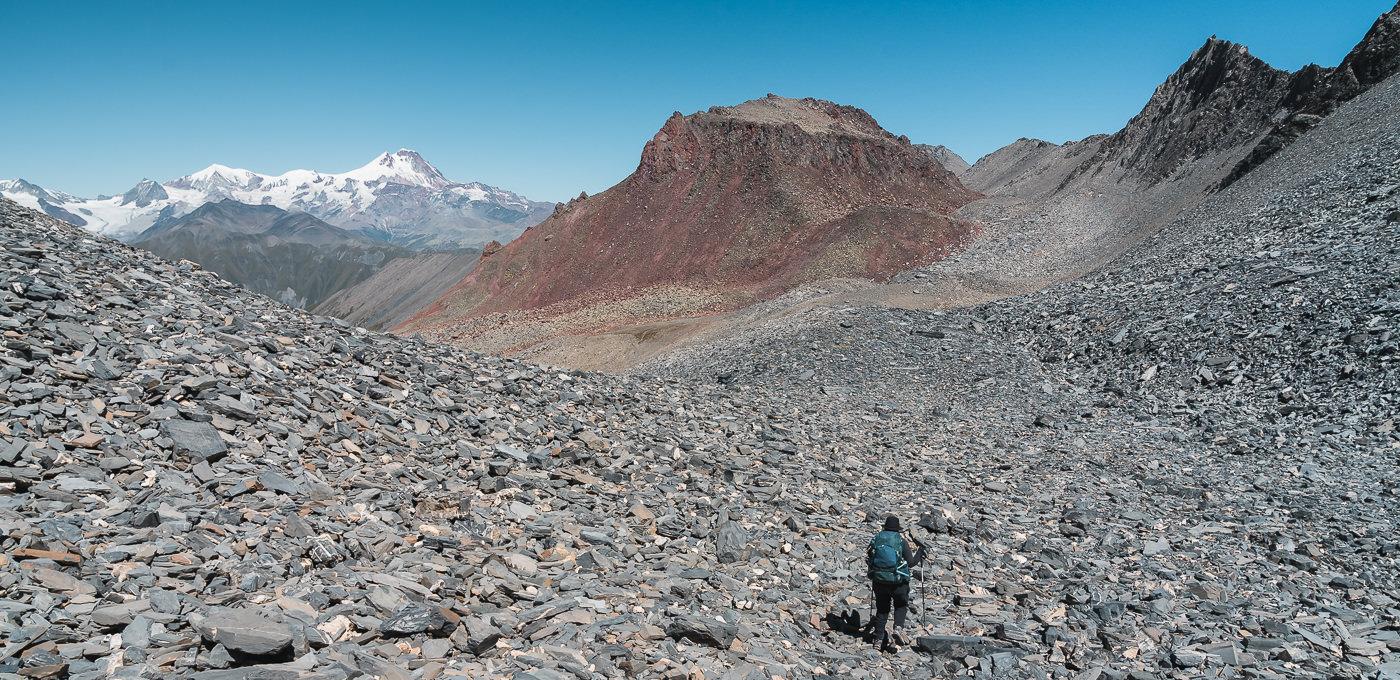 A hiker descends the shale slope from High Esi pass on Day 3 of the Kelitsadi Lake trek