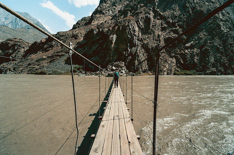 A person stands in the middle of a narrow wooden and wire bridge crossing the Barting River near the Pamir Highway in Tajikistan