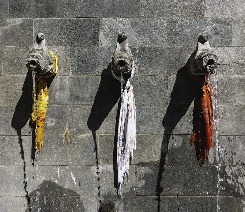 Three stone water taps in a stone wall, tied with one yellow, one white and one red flag