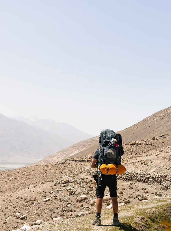 A person with big backpack and tent stands on a narrow trail looking out to the Wakhan Valley below