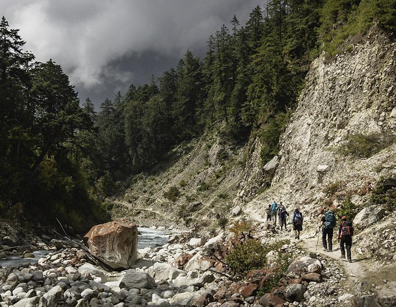 Trekkers hike along the rocky trail by the blue Dudh Khola on the Manaslu Circuit Trek