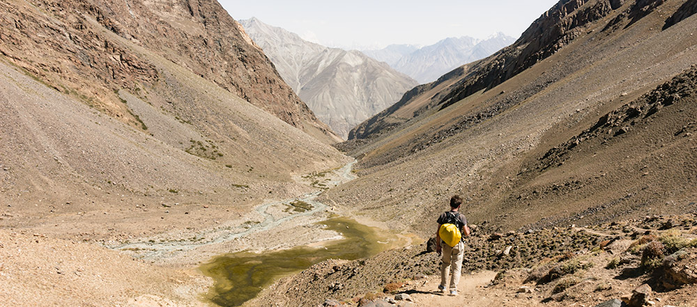 A person stands at the top of the valley leading down from Peak Engels Meadow to Langar, one of the best hikes to do on a Pamir Highway road trip
