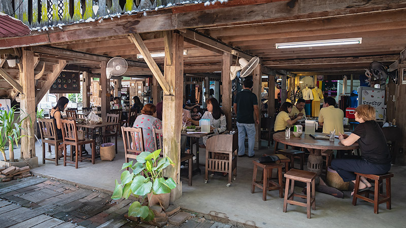 People fill the wooden tables at Huen Jai Yong, one of the best Lanna Cuisine restaurants in Chiang Mai and Northern Thailand