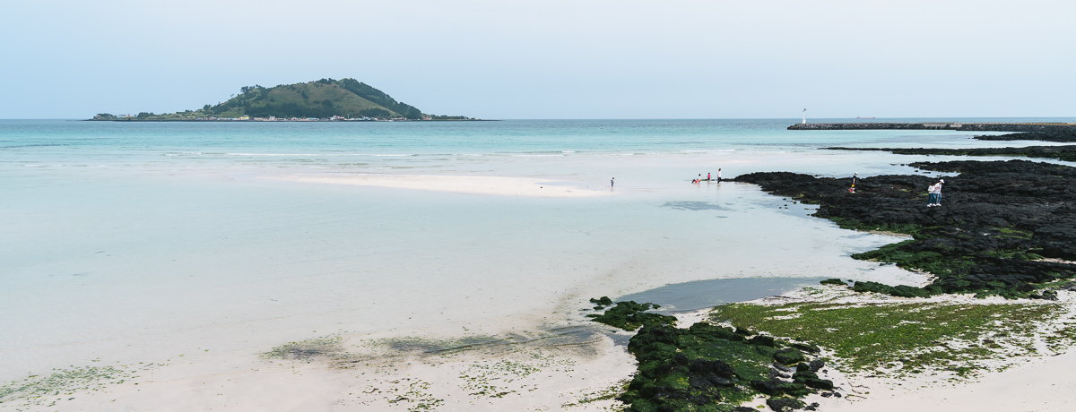 The white sand, black rock and turquoise water of Hyeopjae Beach on Jeju Olle Trail Route 14