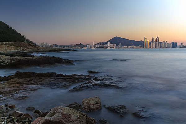 Busan City Guide: Long exposure shot at Igidae Rocks looking over the water to Gwangalli and Haeundae