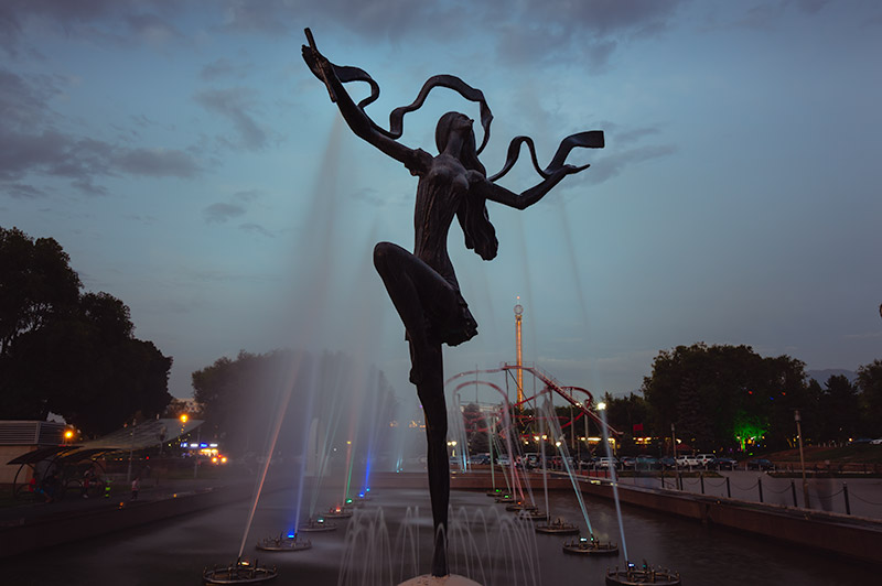 The striking statue in front of the Kazakh State Circus. The statue of a woman performer is surrounded by fountain jets in the growing dusk.