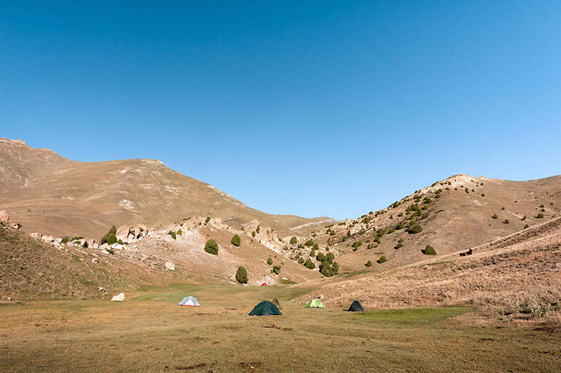 Tents in the high meadow below Tavasang Pass, one of the best campsites while Fann Mountains trekking in Tajikistan