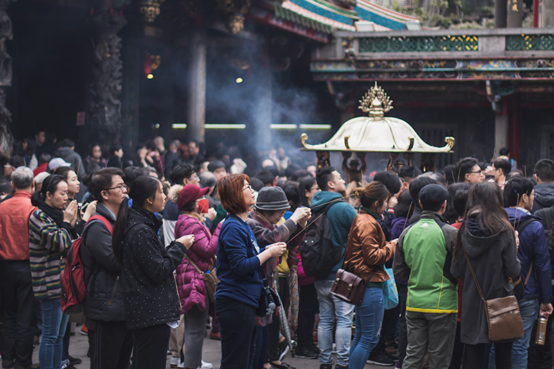 People pray in the courtyard at Longshan Temple, Taipei