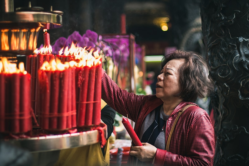 Longshan Temple: a woman lights a candle and incense stack from the stack of flaming candles