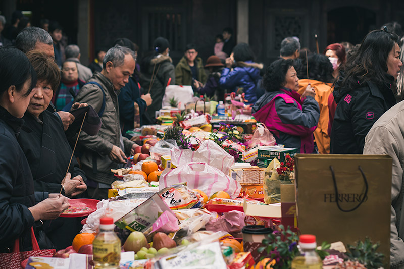Longshan Temple: people leave offerings of food and drink on long tables during Lunar New Year