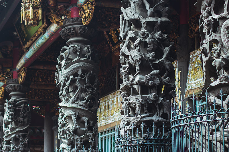 Longshan Temple: intricately carved columns stand outside the main hall, home to Guanyin, goddess of compassion and mercy