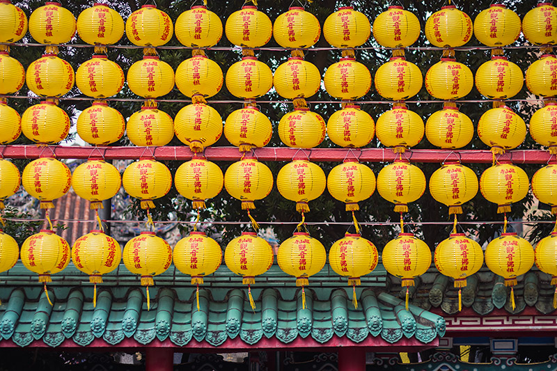 Longshan Temple: rows of yellow lanterns hang above the wall outside the temple