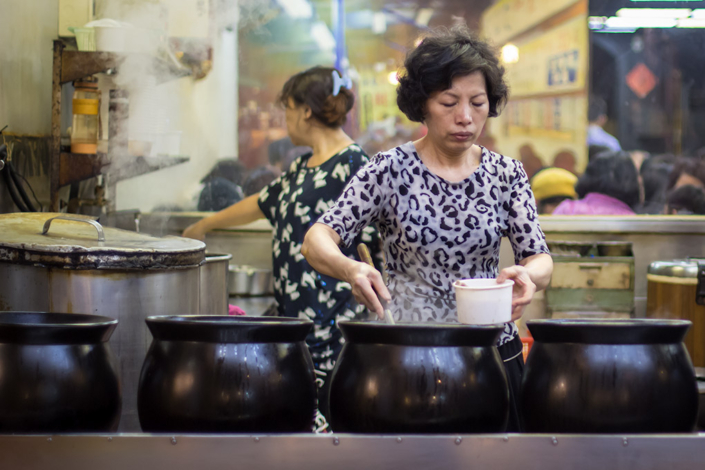 Images of Taiwan: A woman ladles steaming meat broth into a bowl at a packed restaurant near Shilin Night Market in Taipei