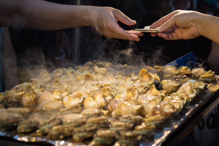 Images of Taiwan: It makes the worls go round. Money changes hands over steaming shellfish at Raohe St. Night Market in Taipei