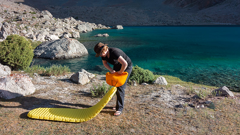 Inflating our Thermarest NeoAir mats at Dushakha Lake while Fann Mountains trekking in Tajikistan