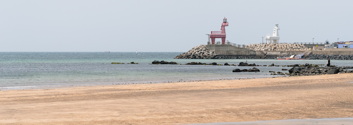 The golden sand of Iho Tewoo Beach near Jeju City, with the red and white ganse pony lighthouses at the end of the pier