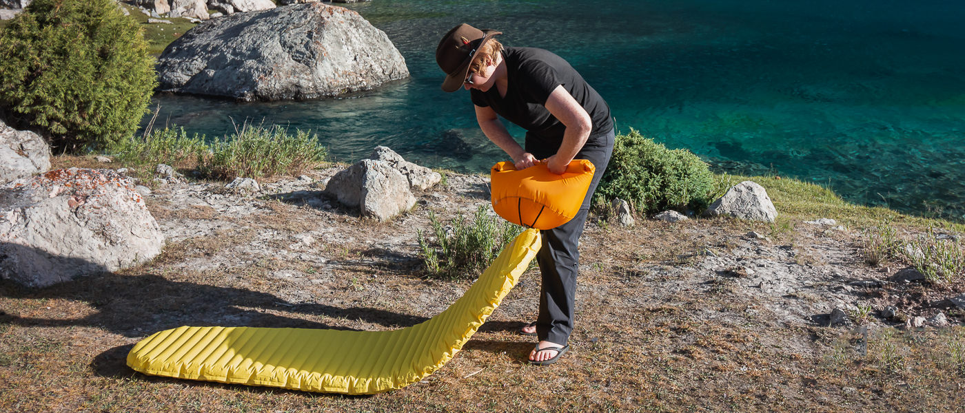 A hiker infaltes her Thermarest NeoAir sleeping pad with a pump sack, both items contributing to a lightweight backpacking camping gear setup