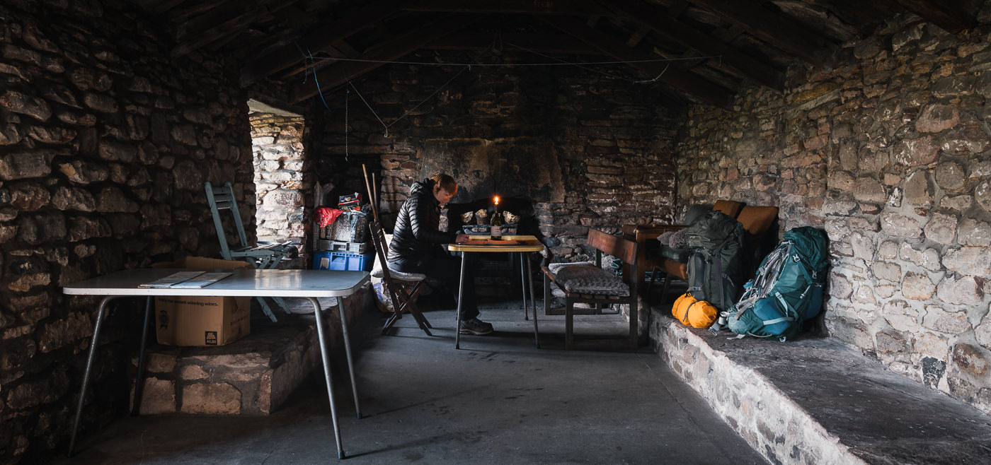 A person sits at the table while writing an entry in the bothy book inside the spacious Burnmouth Bothy on Hoy in the Orkney Islands