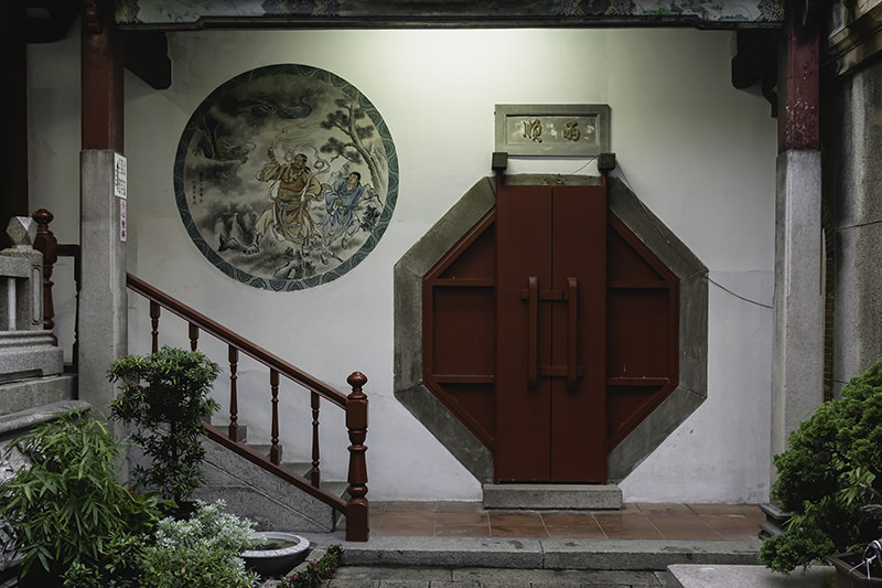 A courtyard area inside the Tainan Grand Mazu Temple, with potted plants, a large hexagonal red door and a circular mural on the wall