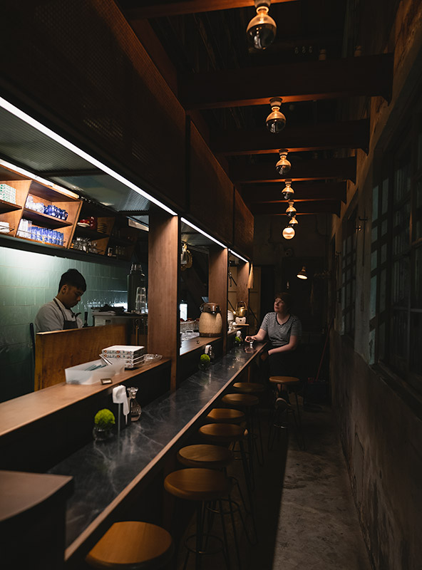 Inside the Japanese restaurant Zyuu Tsubo in Tainan. A person sits at the long counter while a chef prepares food behind the bar