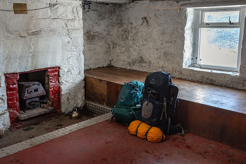 Inside the one room Ryvoan Bothy, bags leaning against the four person sleeping platform