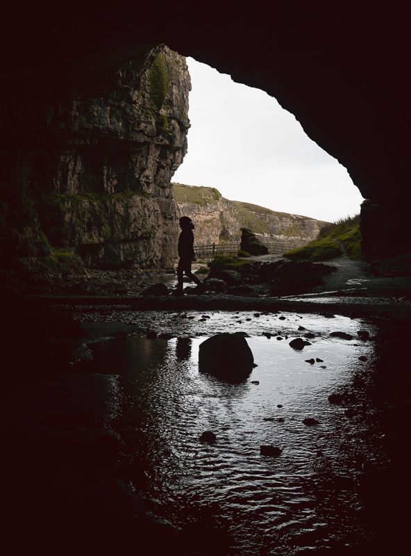 A person walking between rockpools inside the main cavern of Smoo Cave, one of the North Coast 500's must see sights.