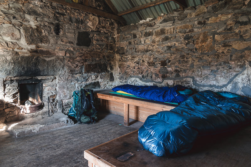 Sleeping bags and mats laid out on the wooden sleeping platforms inside Suileag Bothy