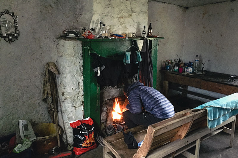 Stoking the fire inside Tomsleibhe Bothy on Mull