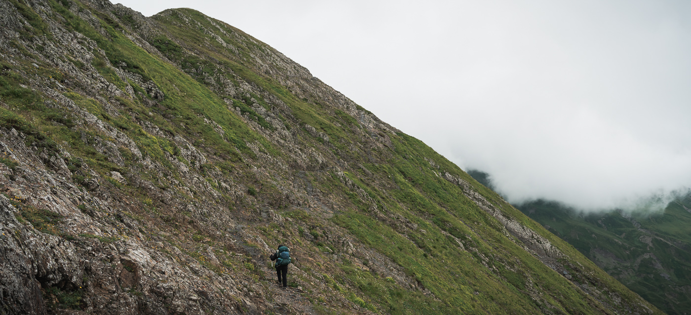 A hiker following the rough trail on the rocky steep slopes on the Iron Mountain Trail on Day 4 of the Tusheti Pankisi trek