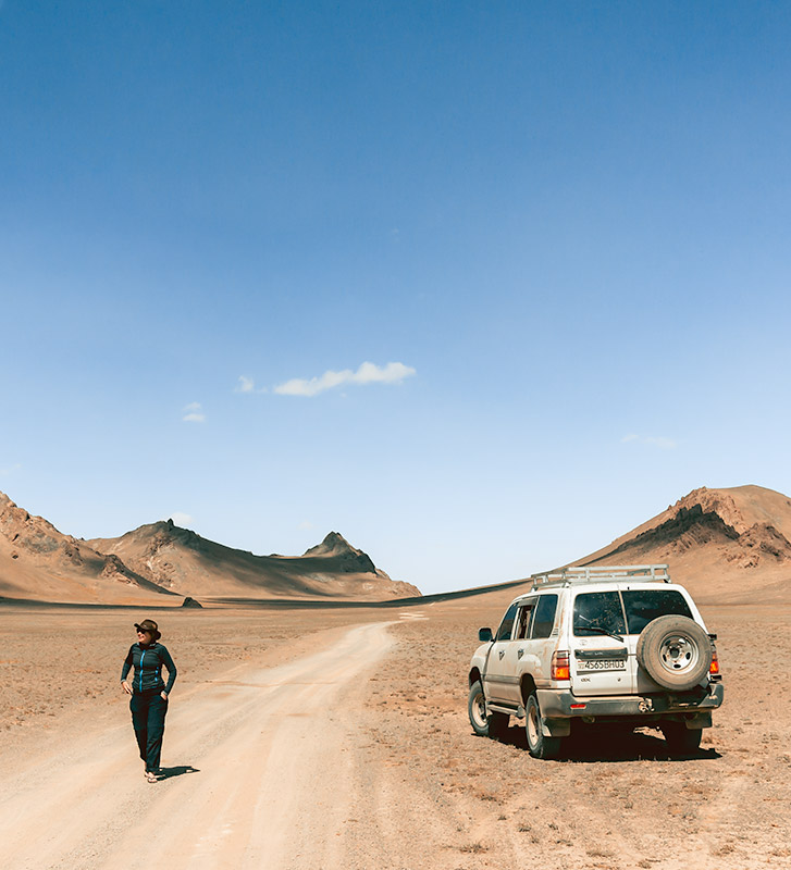 Kim walking near a Landcruiser on a remote stretch of road running through the Pamirs near Jarty Gumbez