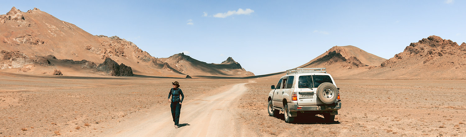 A woman walking near a Landcruiser on a remote stretch of road running through the Pamirs near Jarty Gumbez